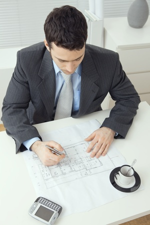 Architect wearing grey suit sitting at office desk, writing notes on floor plan. Overhead shot. photo