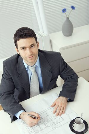 Young businessman, sitting at office desk, planning office layout. Overhead shot. photo