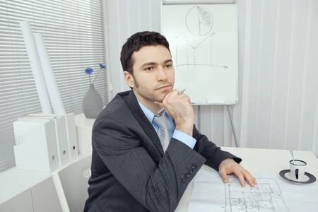 Young businessman thinking over floor plans. photo