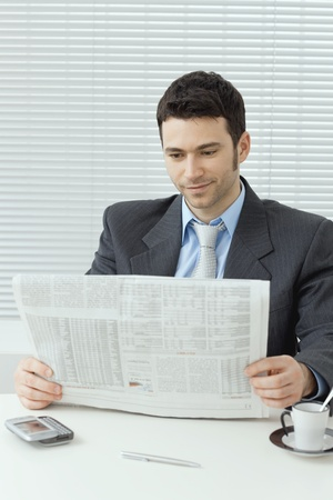 Young businessman having coffee break, sitting at office desk and reading newspaper. Stock Photo - 8895083