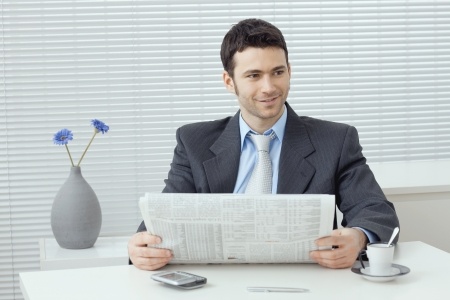 Young businessman having a morning coffee break, sitting at desk and reading newspaper. photo