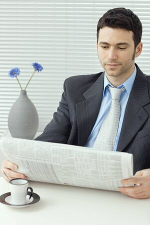 Young businessman having a morning coffee break, sitting at desk and reading business news. Stock Photo - 8907762