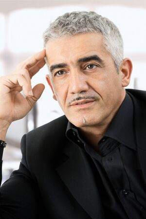 Mature gray haired creative looking businessman thinking. photo