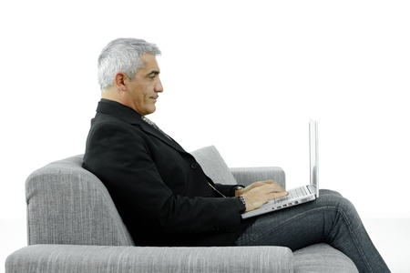 attire: Profile potrait of mature businessman sitting on couch, using laptop computer. Isolated on white.