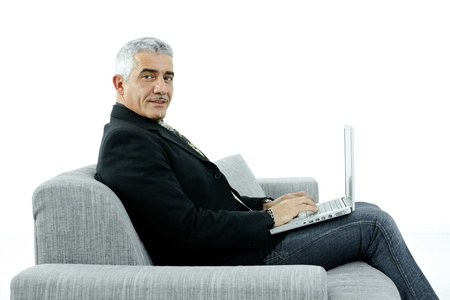Mature businessman sitting on sofa, using laptop computer, smiling. Isolated on white. photo