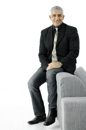 Portrait of creative looking businessman wearing jeans and black jacket, sitting on couch. Isolated on white. photo