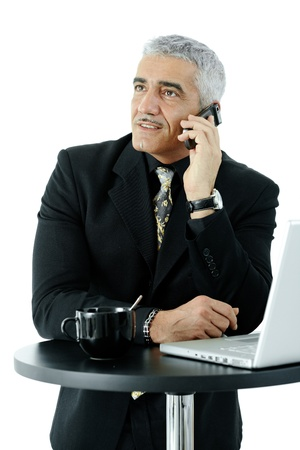 gratified: Mature businessman standing at coffee table, talking on mobile phone. Isolated on whte.
