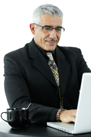 Happy mature businessman working on laptop computer, smiling, isolated on white background.