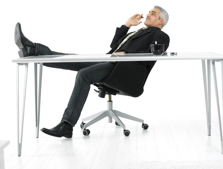 Mature businessman sitting at desk in confident pose, smoking cigar. Isolated on white. Stock Photo - 8894596