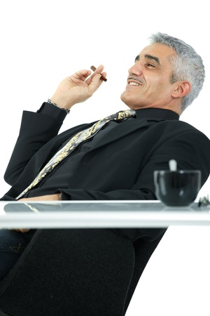 Confident mature businessman sitting at desk leaning back, smoking cigar. Isolated on white. photo