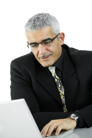 Mature businessman sitting at desk, using laptop computer, looking at screen. Isolated on white. photo