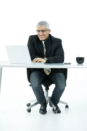 Mature businessman sitting at office desk, working on laptop computer. Isolated on white. photo