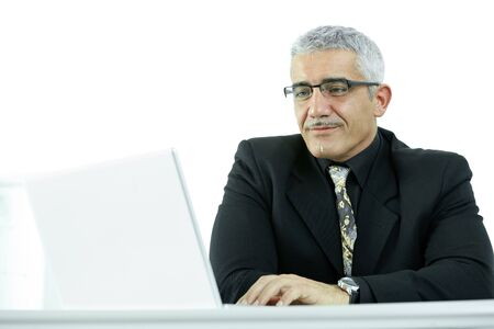 Mature businessman sitting at desk, using laptop computer, smiling. Isolated on white. photo
