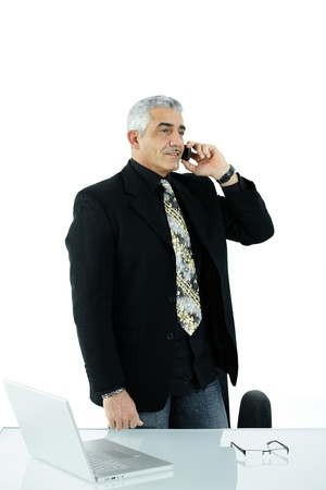 gratified: Gray haired mature businessman calling on mobile phone, smiling, isolated on white background.