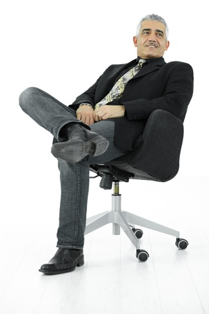 1 adult only: Portrait of mature businessman sitting in office chair in confident pose. Isolated on white.
