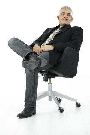 hombre sentado: Retrato de empresario maduro, sentado en la silla de oficina en pose de confianza. Aislados en blanco.