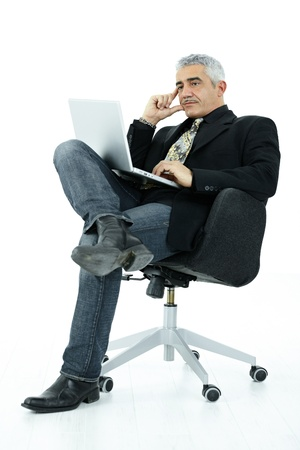 undoubting: Mature businessman sitting in office chair working on laptop computer, serious look, isolated on white background.