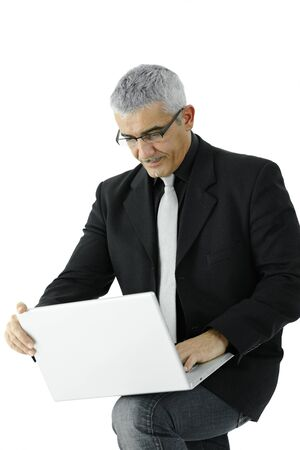 Mature businessman standing, holding laptop computer on his knee. Isolated on white. photo