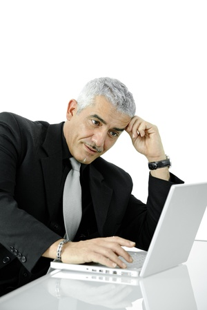 Troubled businessman using laptop computer, leaning on hand, looking at screen. Isolated on white. photo
