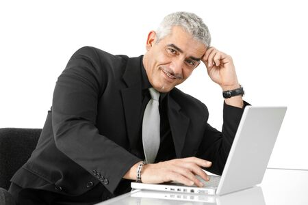 Mature businessman working on laptop computer at office desk, smiling, isolated on white background. photo