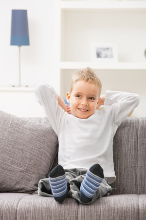Happy relaxed young boy wearing white t-shirt, sitting at couch, looking at camera, smiling. photo