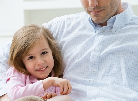 Portrait of little girl wearing pink dress sitting on couch embraced by her father, smiling. Stock Photo - 8908600
