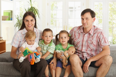 2 3: Portrait of happy nuclear family with 3 children sitting on sofa at home, looking at camera, smiling.