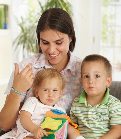 Happy mother sitting on couch at home with two cute children. Stock Photo - 8908930