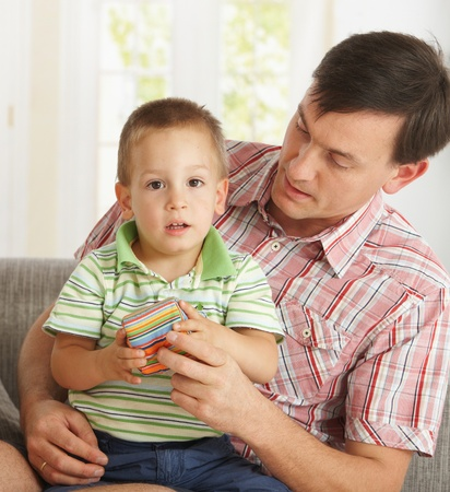 Father and son sitting on couch at at home playing together Stock Photo - 8895321