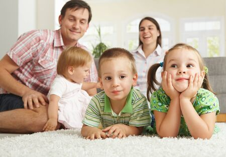 Happy family with 3 children sitting on floor of living room at home. photo