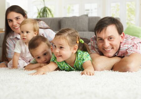 cosy: Happy family having fun posing on floor of in living room at home.
