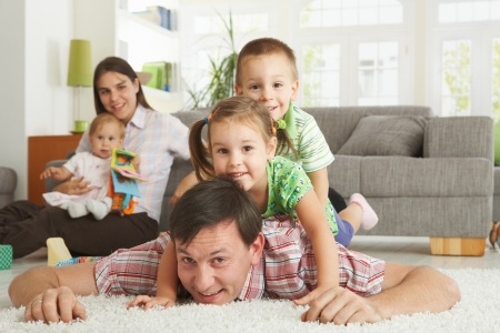 Happy family having fun posing for camera on floor of in living room at home, looking at camera, smiling. Stock Photo - 8906547