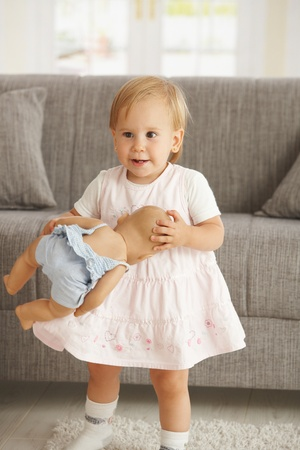 Cute little toddler girl standing in living room holding dolly, smiling. photo