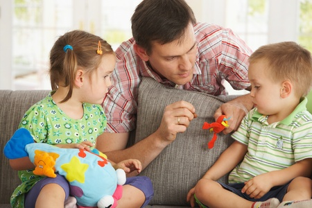 Father playing with children on couch at home. Stock Photo - 8908894