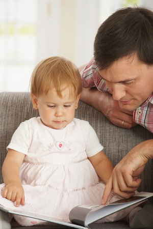 Father and toddler reading book on sofa at home. Stock Photo - 8906539