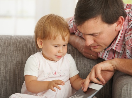 Father and toddler looking at book on sofa at home. Stock Photo - 8906543