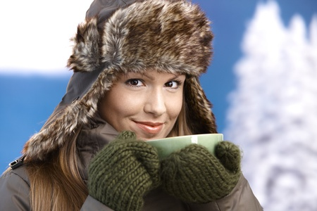 blue grey coat: Young attractive female dressed up warm in coat, fur-hat and gloves, drinking hot tea, smiling.