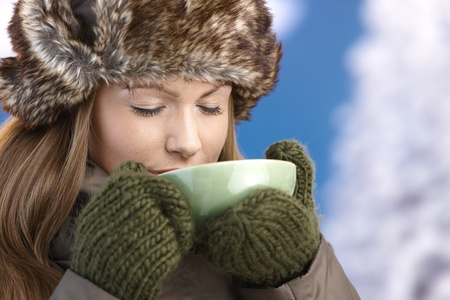 offish: Young attractive female dressed up warm in coat, fur-hat and gloves, drinking hot tea, eyes closed.