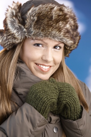 Pretty young girl dressed up warm in coat, fur-hat and gloves, smiling after skiing. photo