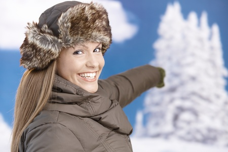 Young attractive woman dressed up for winter fun in coat and fur-hat, enjoying winter, smiling and pointing to snowy background. photo