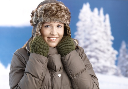 Pretty young girl dressed up warm in coat, fur-hat and gloves, smiling front of winter landscape. photo