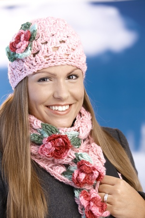 Pretty young girl dressed up warm in coat, cap and scarf, smiling front of winter landscape . photo