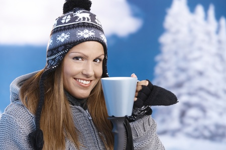 Pretty young girl dressed up warm for skiing wearing cap and gloves drinking hot tea smiling front of winter landscape . photo