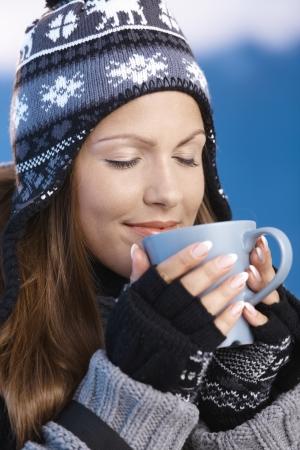 ropa de invierno: Bastante joven vestido caliente vistiendo gorra y guantes beber bebida caliente ojos cerrados frente de paisaje invernal de esqu�.