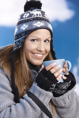 Attractive young female dressed up warm for skiing wearing cap and gloves drinking hot tea smiling front of winter landscape . photo