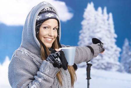 front teeth: Attractive young female skiing, resting, drinking hot tea, pointing to winter landscape, smiling. Stock Photo