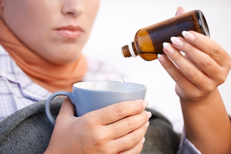 Young woman at home having flu, feeling bad, taking medicine, vitamin, drinking hot tea in bed. photo