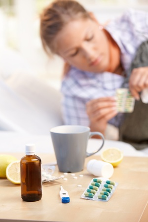 Vitamins, medicines, hot tea and lemons in front, woman caught cold taking medicines in background. Stock Photo - 8895477
