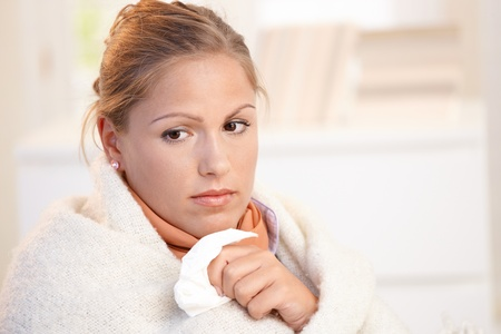 Young female having flu, feeling bad, wrapped up in blanket. Stock Photo - 8895490