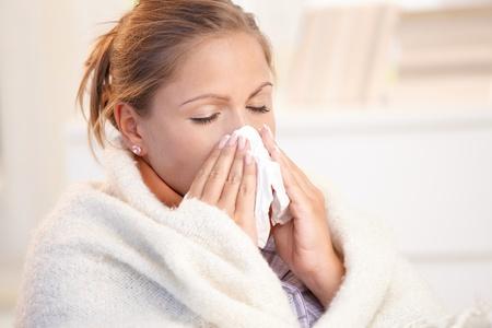 ragazza malata: Giovane donna avere influenza, sentirsi male, soffiando il naso, avvolto in coperta.
